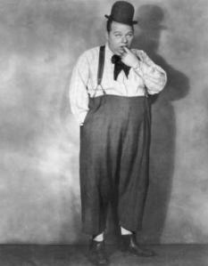 circa 1920: A full-length studio portrait of the silent screen comedic actor Fatty Arbuckle (1887-1933) wearing a black hat and sticking his finger in his mouth. (Photo by Mitchell/Hulton Archive/Getty Images)
